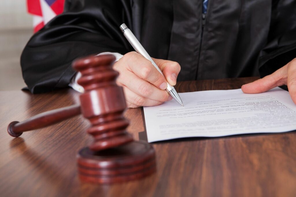 gavel on desk with person writing