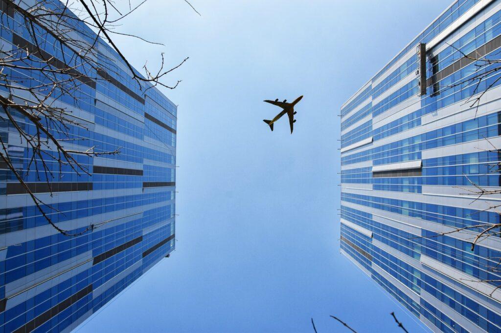 Looking up at airplane between buildings