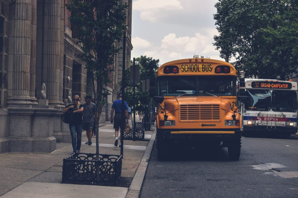 School bus and public bus on street