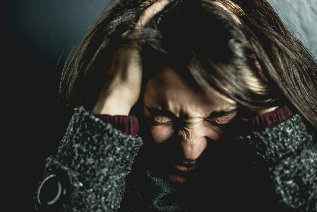 Woman in Pain Holding Head - Brain Injury Headache Anxiety