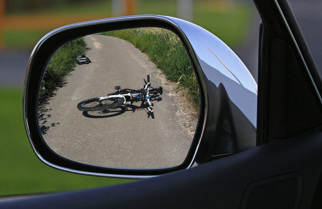 Bike accident in side mirror of car.