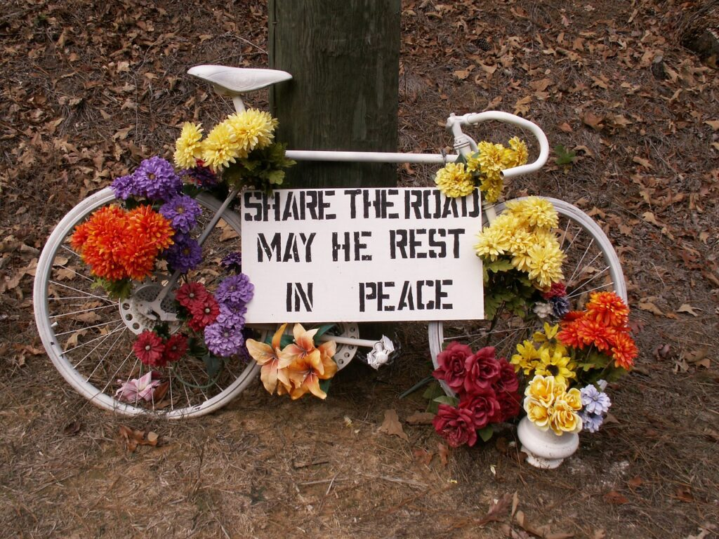 Bike accident memorial with bike and flowers and sign, Share the Road May He Rest in Peace